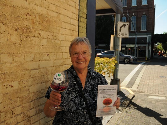 Carol Snyder holds a glass of fake pinot noir, but
