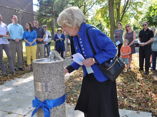 Jeanne McCue takes the first sip of water out of a water fountain during a rededication ceremony Oct. 8. Her son Daniel McCue contributed $500 for the drinking fountain shortly before he died in 1989 at the age of 27.