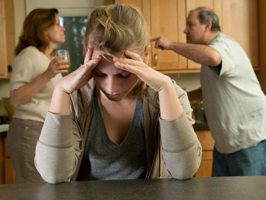 Girl holding head while parents fight in background