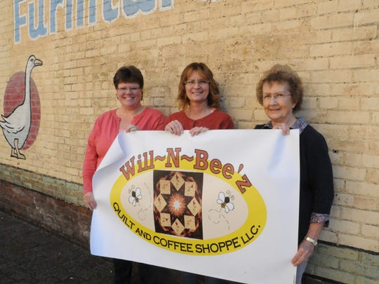 From left, Mary Williams, Becky Brinlee and Dee Williams, hold a banner for their new project, Will-N-Bee'z Quilt and Coffee Shoppe, which is opening Wednesday, Nov. 1.