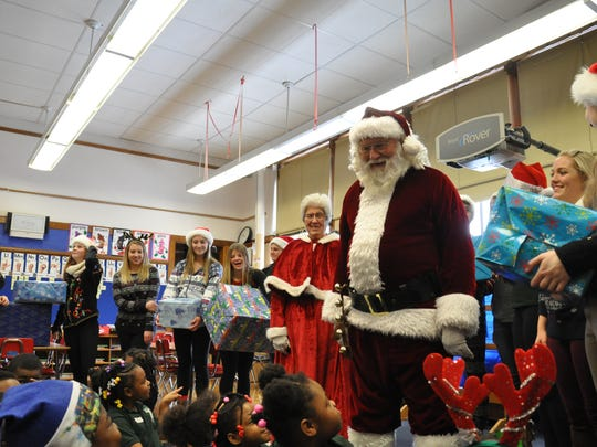 Santa and Mrs. Claus (aka Bob and Gina Magnus) and Oconomowoc High School DECA students deliver gifts during the 2016 Adopt A School program.