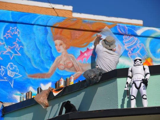 Tim Schubert works on his mermaid mural from the roof of Art & Atiques. The buildings of the Eau Gallie Art District are becoming canvases for local, national and international mural artists for the Anti Gravity Project.