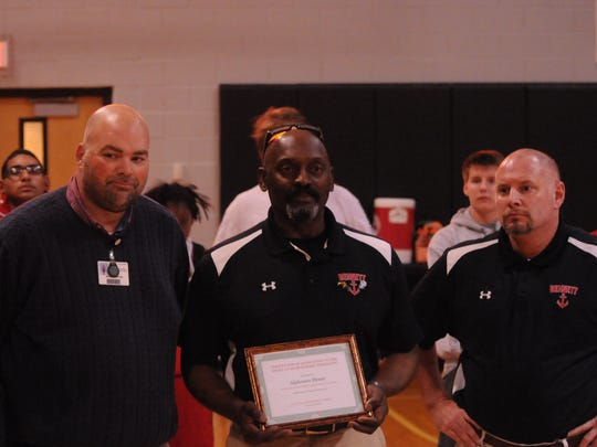 Henry is presented with his Hall of Fame plaque by James M. Bennett faculty.