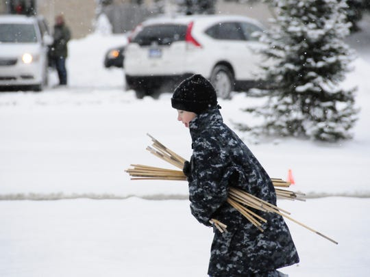 Jacob Rhude of the US Naval Sea Cadets Corps, brings a bundle of dowels to people preparing for the 2017 Wreaths Across America event at Allied Veterans Cemetery in Port Huron.