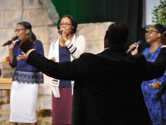 Rev. John Russell raises his hands during a worship