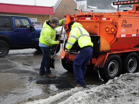 Jason Bobcean and Tom Tramski fill a large pothole