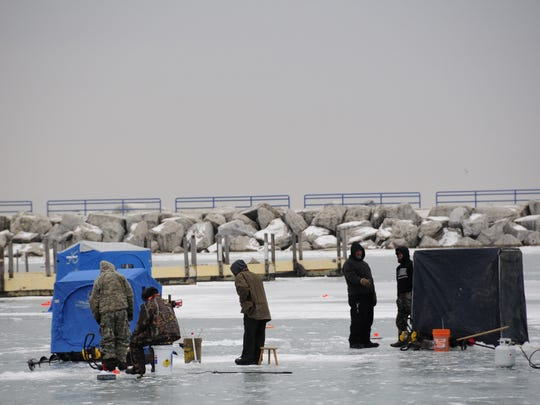Anglers gather on the ice of Lexington Harbor during an ice fishing contest.