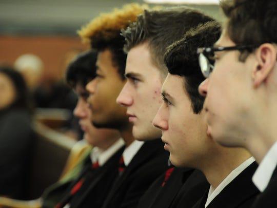 Cardinal Mooney students Preston Witkowski, left, Matt Kalbaugh, Matt Huculak and Wilson Lombard listen to Archbishop Allen Vigneron.