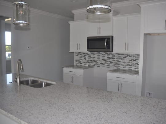 The kitchen has a long wide countertop island that also serves as an eating area.
