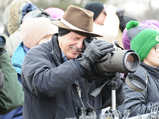 Tom Dennis uses a spotting scope to look for birds during a Winter Bird Blast.