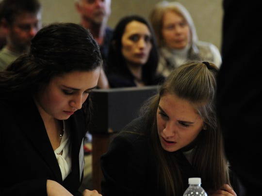 Alysse Armstrong. left, and Delaney Ward of Port Huron Northern check their notes during Mock Trial