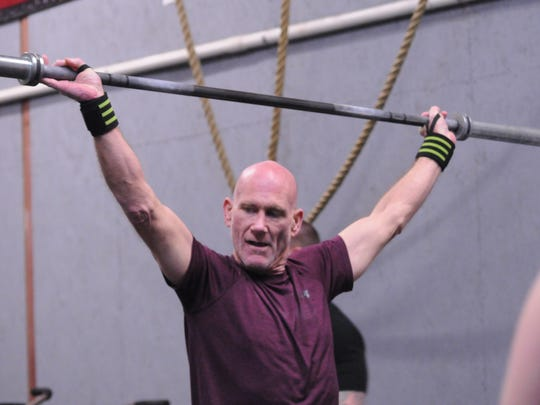 """James Waller takes part in the Irong Strong CrossFit gym's """"Friday Night Lights"""" on Mar. 9, 2018."""