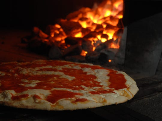 A pizza is ready to be pulled out of the oven at Cassie's
