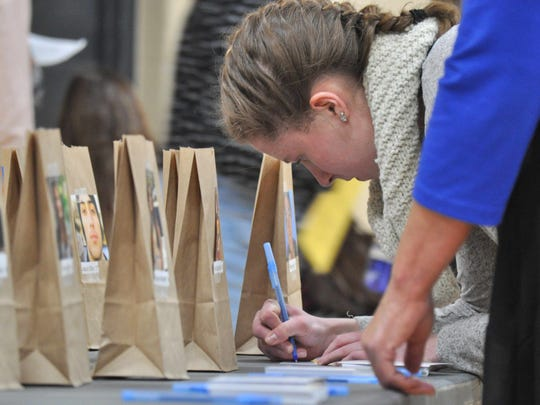 Germantown High School senior Ellie Decker on March 14 fills out letters to the families of victims who died during the shooting at Marjory Stoneman Douglas High School on Feb. 14 in Parkland, Florida. Decker was one of hundreds of students in the Germantown High School gym for an assembly planned by students and staff to address mental health and school safety.