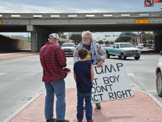 Jordan Shafer, 71, of Plano, left, and his 10-year-old grandson Braylon Shafer stop to take a picture with Gale McCray of Fort Worth in Abilene on Thursday. Shafer follows McCray's Facebook page Old Man With a Sign.