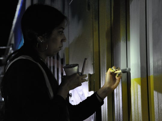 Senior Elizabeth Hinojosa, 17, from Grand Prairie Fine Arts Academy uses the light from her cell phone to paint details on a mural at 301 Locust St. on March 24. The students worked around the clock to compete the 900-square-foot mural in two-and-one-half days.