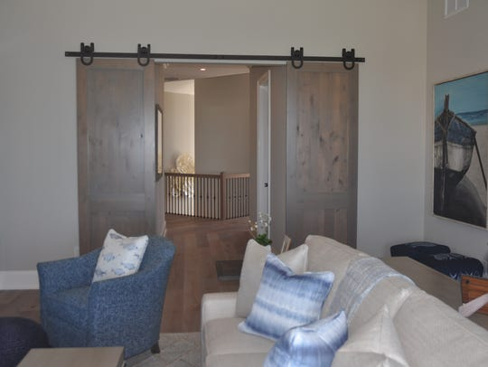 Barn doors lead to a fourth floor living room with