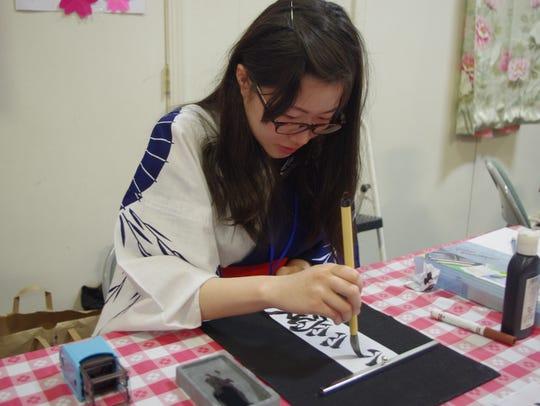 Fusako Kurohashi writes a Japanese message for a visitor