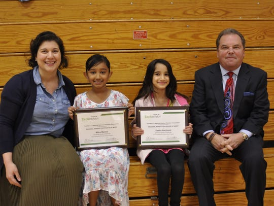 University School of Nashville teacher Victoria Roca (left) and Toshiba southern region sales director Cary Butler (right) congratulated Hendersonville natives Mithra Menon and Eesha Nachnani for winning the regional ExploraVision award for their C2 project addressing global warming.