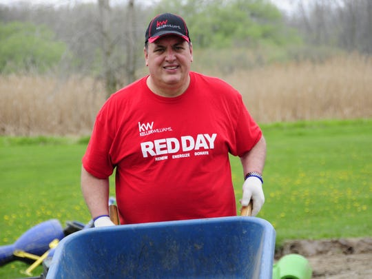 Phil Grosso, with Keller Williams Platinum, picks up debris Thursday, May 10, 2018  left from winter flooding at Memorial Park in Port Huron Township.