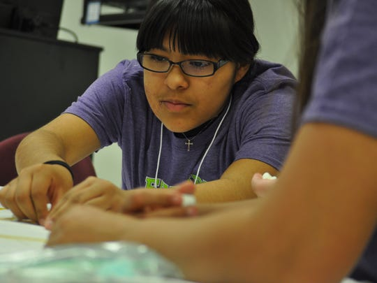 Allison Quintela, a seventh grader at Carlsbad Middle school, uses spaghetti and marshmallows to construct a structure during a workshop May 10.