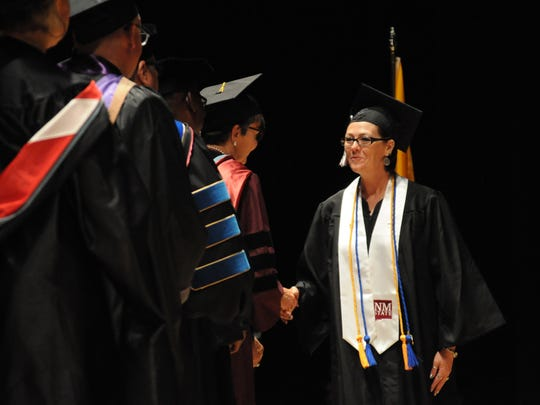 Kristie Worden walks across the stage to receive her degree at the 43rd annual New Mexico State University Carlsbad commencement Thursday, May 10, 2018