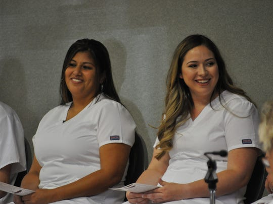 Nursing graduates Amanda Lozoda and Kaila Mallett sit during the nurse pinning ceremony Friday, May 11, 2018.