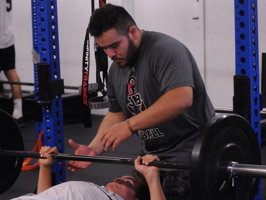 Assistance coach Ricardo Bravo spots an athlete during a bench press set at The Athlete Academy on May 16, 2018.
