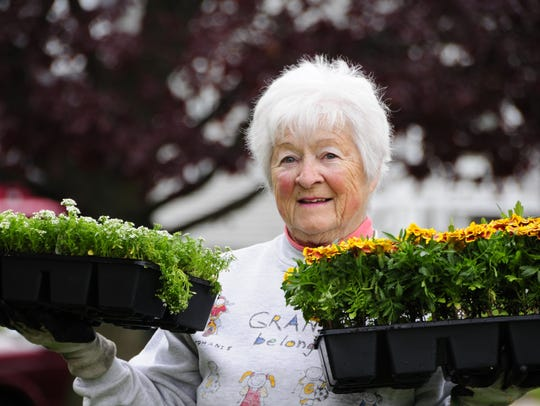 Donna Kelly carries two flats of plants at River Park