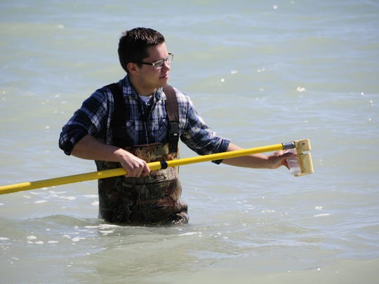 Adam Czubachowski collects a water sample for testing