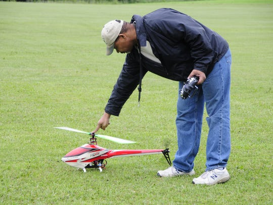 Carl Jones of Kimball Township collects his radio-control helicopter during the St. Clair County Propbusters fly-in Saturday, June 9, 2018 at Goodells County Park.