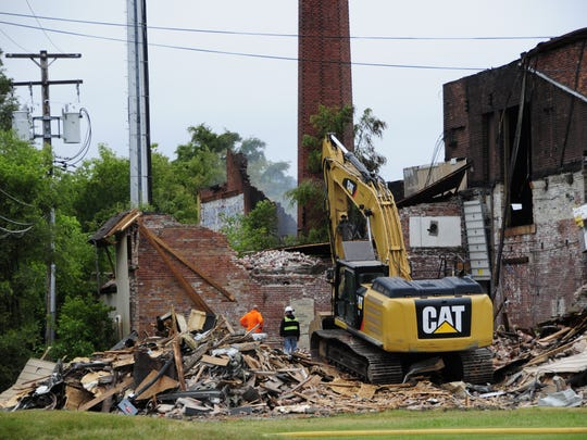 A large excavator digs into the rubble pile at the former Chicory Warehouse on 12th Avenue in Port Huron.