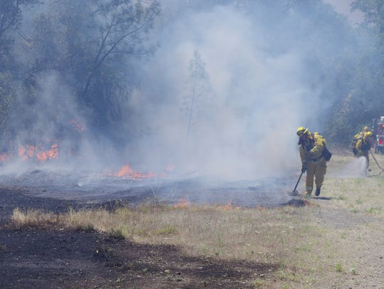 Firefighters work on one of five fires that burned
