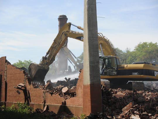 An excavator knocks down a piece of the wall at the