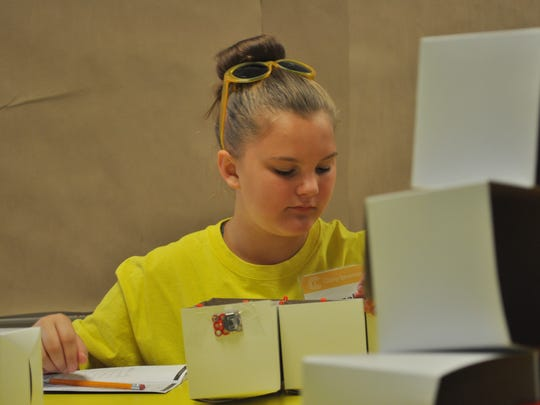 Hannah, 11, works on her modular mansion at Camp Invention