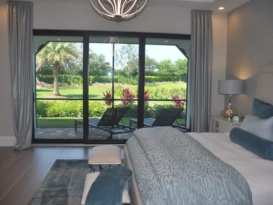 The master bedroom has views of the lanai and gardens.