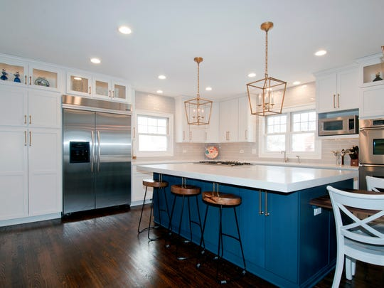 A Kitchen Tune-Up project included the refacing of a navy island and the addition of new cabinets and countertops.