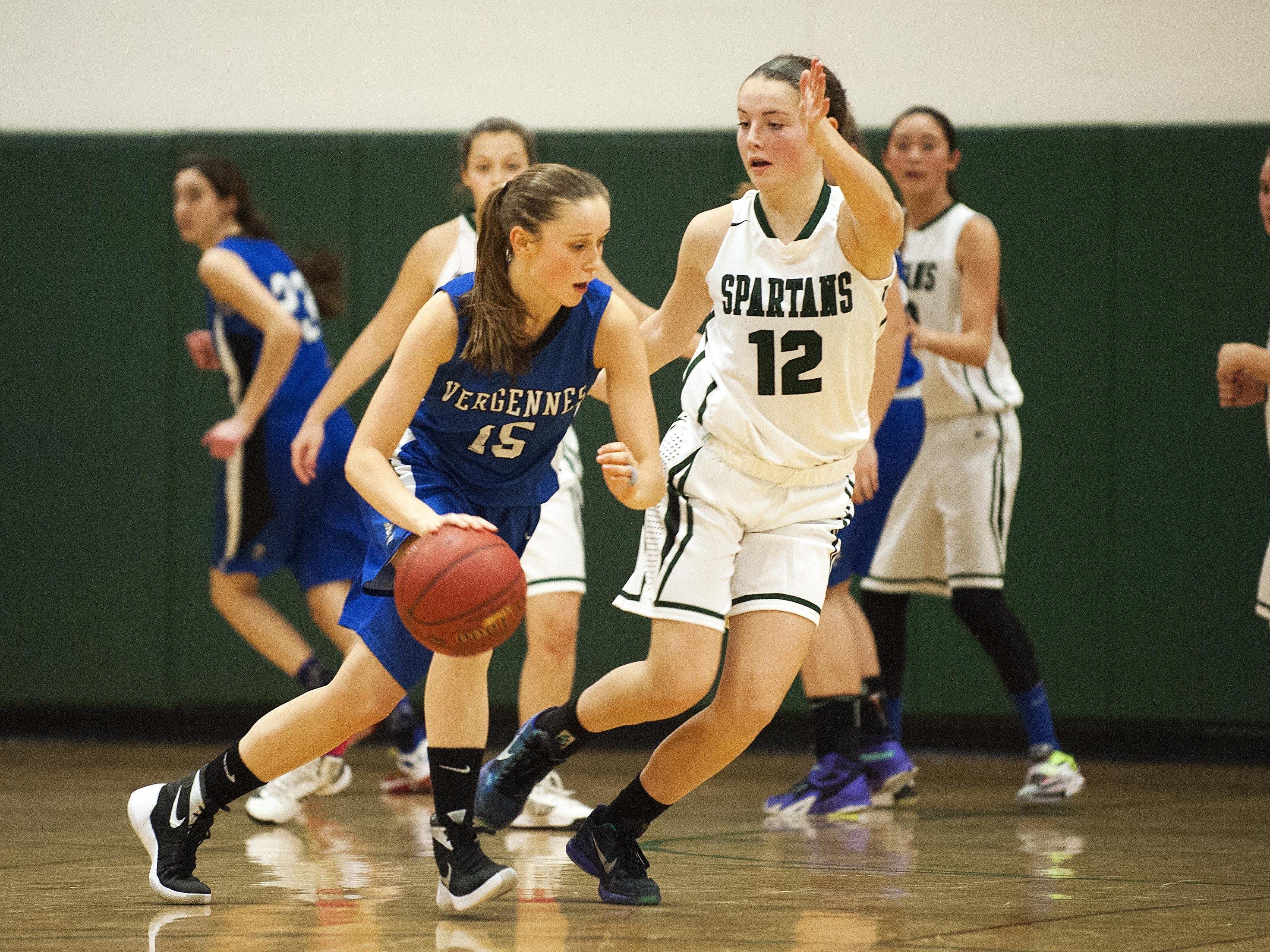 Vergennes' Caroline Johnston (15) dribbles the ball around Winooski's Lydia Nattress (12) during the girls basketball game at Winooski High School on Wednesday.
