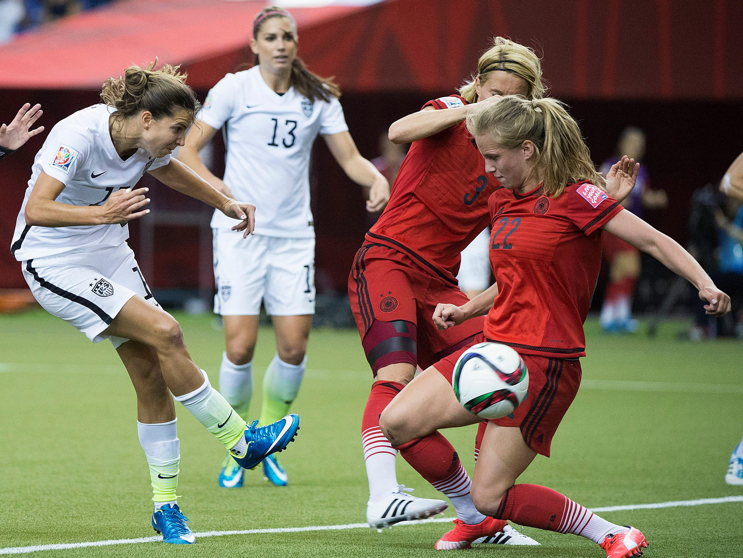 United States' Tobin Heath, left, has a shot blocked by Germany's Tabea Kemme (22) during the first half of a semifinal in the Women's World Cup soccer tournament, Tuesday, June 30, 2015, in Montreal, Canada. (Graham Hughes/The Canadian Press via AP)