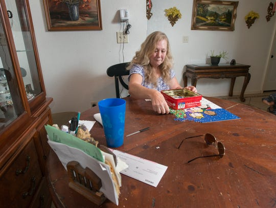 Cheryl Kursave disassembles a puzzle at her house in