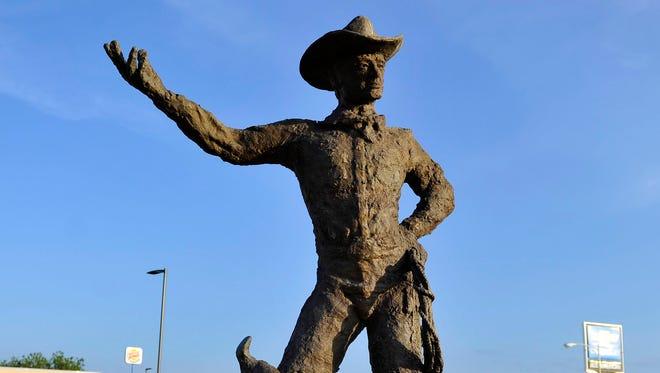 A bronze cowboy sculpture located on Bryant Blvd and 3rd St. by artist Scott Sustek.