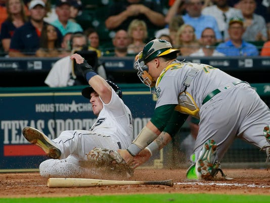 Oakland Athletics catcher Bruce Maxwell tags out Houston Astros' Alex Bregman out at home on the throw from center fielder Boog Powell in the fifth inning of a baseball game Saturday, Aug. 29, 2017, in Houston. (AP Photo/Richard Carson)