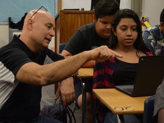 Russell Eves, an eighth grade U.S. History teacher at Nellie Coffman Middle, helps a student with an assignment. He has instructed his students to pick a candidate to support - Hillary Clinton or Donald Trump.