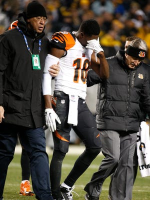 The Cincinnati Bengals wide receiver A.J. Green (18) is helped off the field after taking a hit in the fourth quarter against the Pittsburgh Steelers at Heinz Field. The Enquirer/Jeff Swinger
