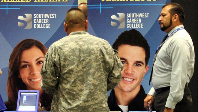 Admissions adviser Genaro Lopez, right, of Southwest Career College shows a soldier information at the semiannual Hiring Fair in 2012 at Fort Bliss.