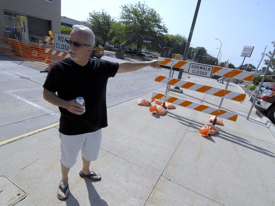 Pat Matter, standing on the sidewalk across from the Webster County Iowa Law Enforcement Center in downtown Fort Dodge, points to where some of the old bars once stood. His friend Rick Wingerson was shot to death in 1974 near where Matter is standing.