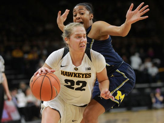 Iowa's Kathleen Doyle drives past Michigan's Deja Church