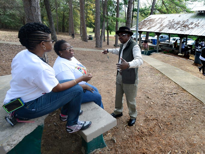 LaDonna Davis, from left, Tralisa Jones and Willie Robinson, Jr., chat as people arrive for the Highland Community Fun Day at North Highland Park in Prattville, Ala. on Saturday March 22, 2014.