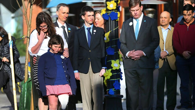 Boston Mayor Marty Walsh, right, looks down after Boston Marathon survivor Jane Richard, left, and her brother Henry remove a drape covering a memorial honoring victims and survivors at one of two blast sites near the finish line of the Boston Marathon in Boston, Wednesday, April 15, 2015. Parents, Bill and Denise Richards, back, stand by during the unveiling. The children lost their brother Martin Richard while standing with him during one of the explosions.