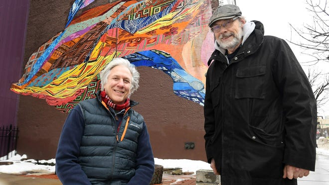 Erie artists Tom Ferraro, left, and Ed Grout are shown in January 2019 in front of the mural they designed and installed on the north side of the former Palace Hardware building, 913-915 State Street. It's one of numerous public art projects they have been involved with in the Erie area.